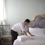 a person fixing a bed