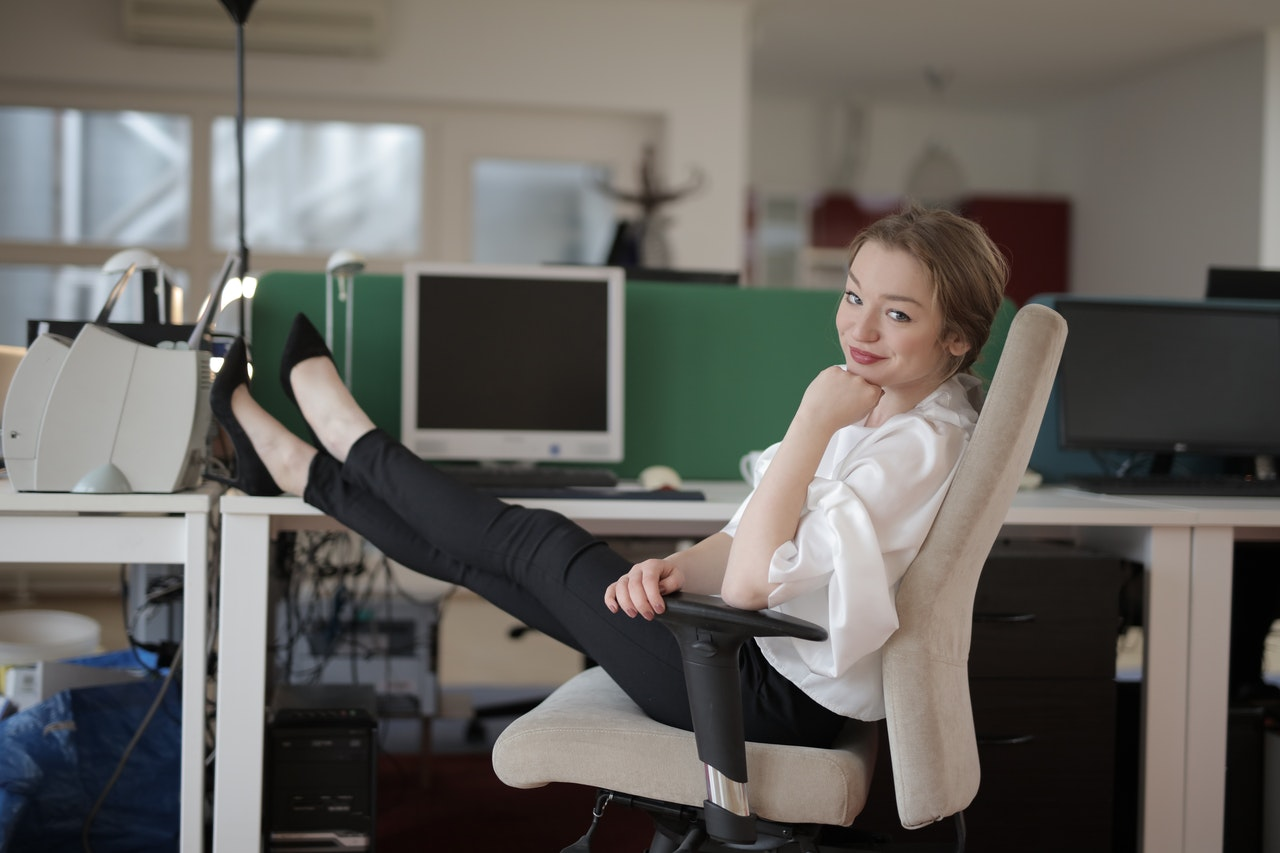 A woman sitting in an office chair with legs on the table