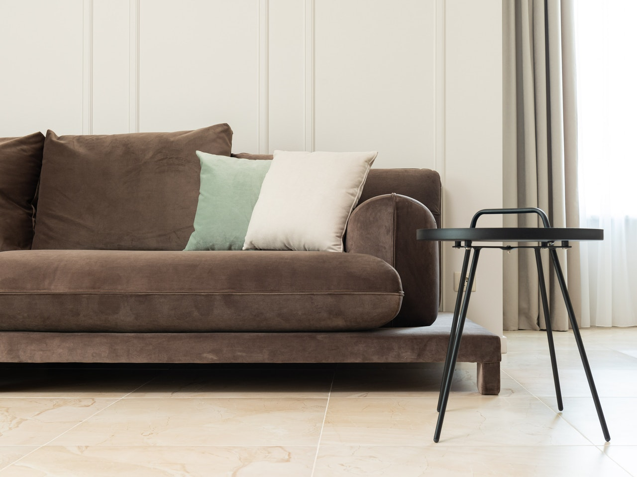 A stool next to a clean microsuede couch