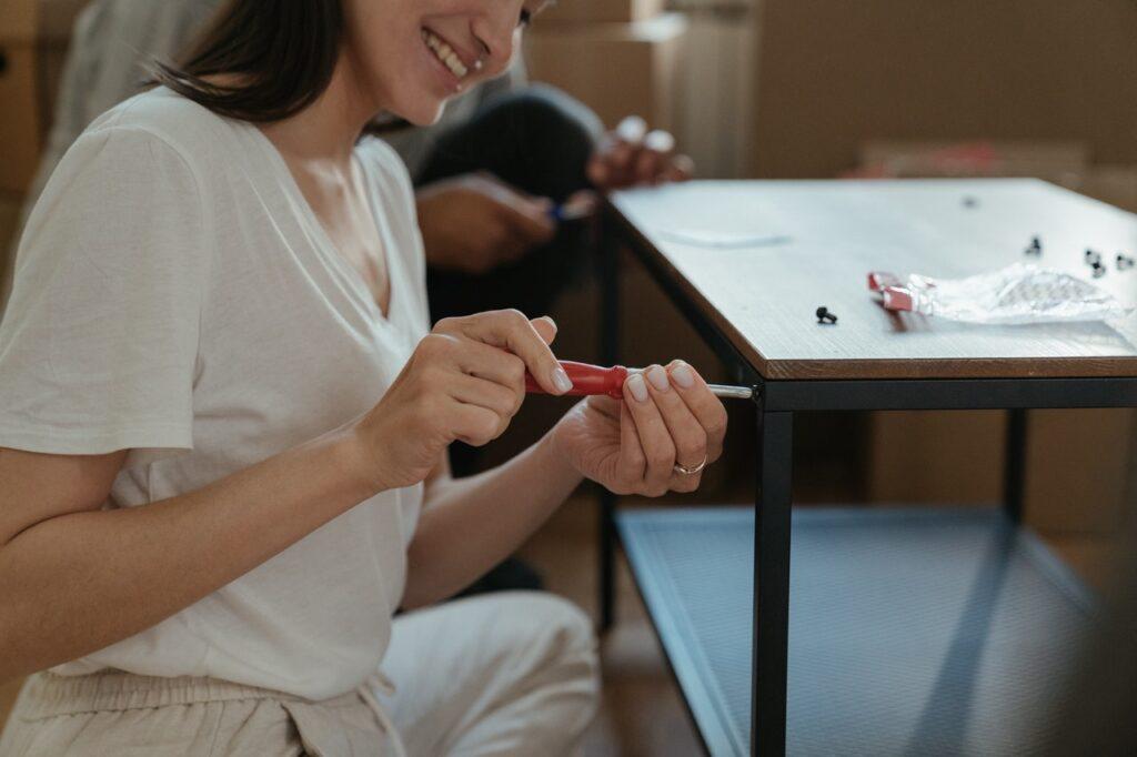 A woman restoring furniture/ A woman assembling furniture