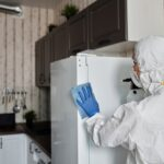 A person in a cleaning suit cleaning a refrigerator